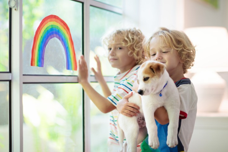 two little boys look out a window while in quarantine