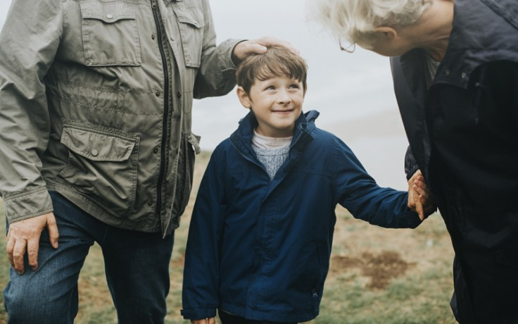 little boy from wales holding grandparents' hands