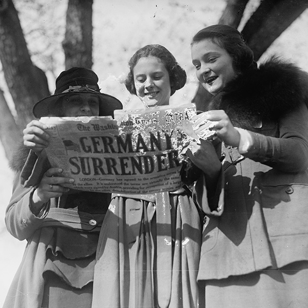 girls hold newspaper signaling end of WWI, a significant event in ww1 timeline