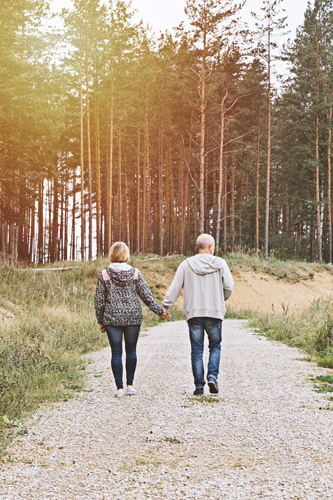 couple holding hands in woods