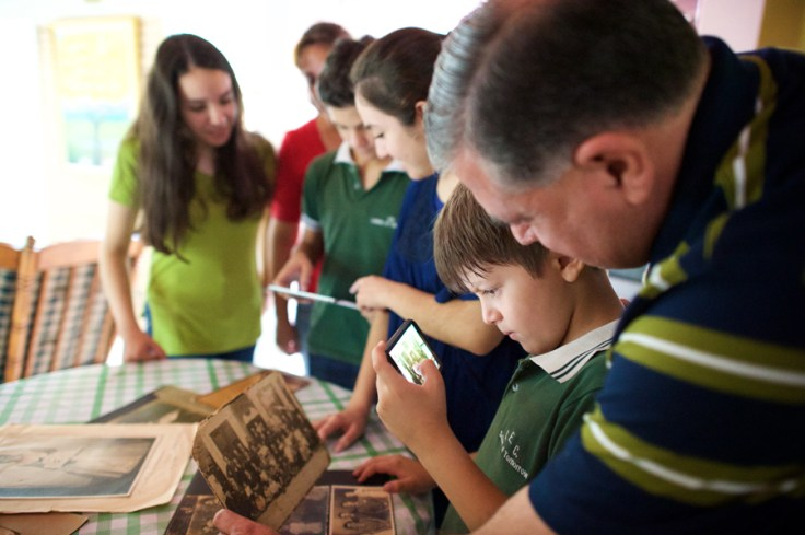 Boy digitizing family history photos.