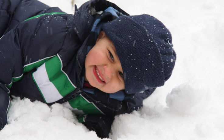 a boy plays in the snow, a weather that would be considered brass monkeys.