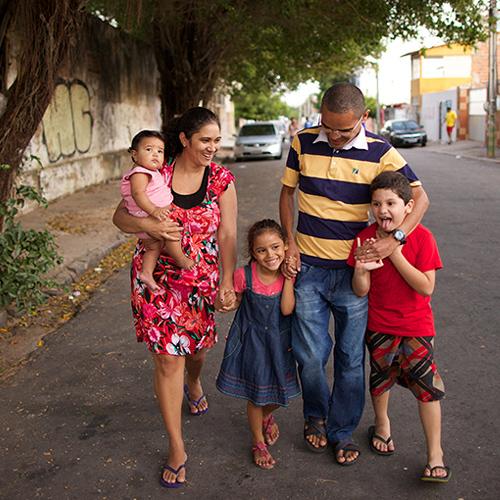 Família brasileira andando por uma rua.