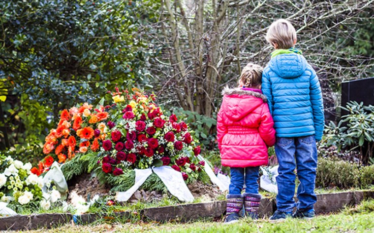 Boy and girl standing at memorial of their loved one.