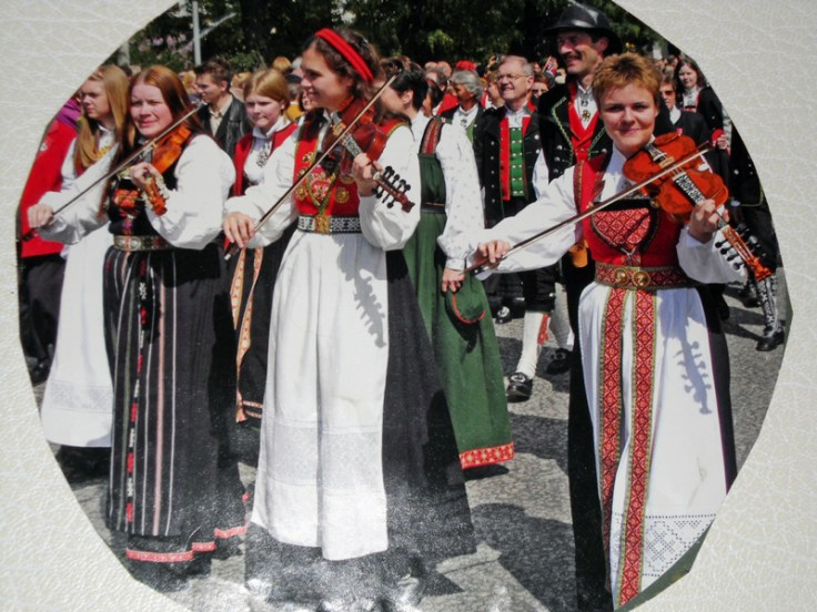 Norwegians wearing traditional Norwegian dress and playing violins