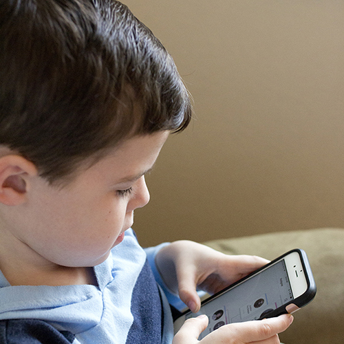 Un chico mira un teléfono