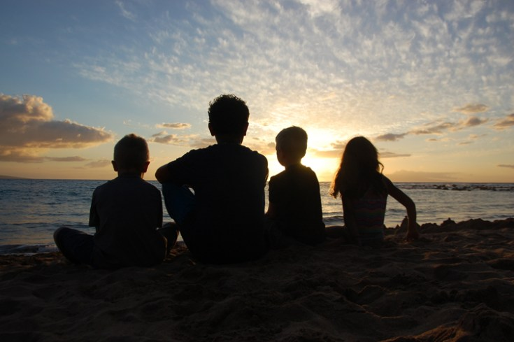 children on a beach look out to the ocean during sunset.