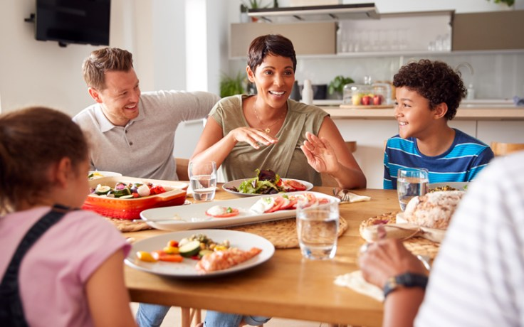 Family plays thanksgiving activity, sits around the table smiling