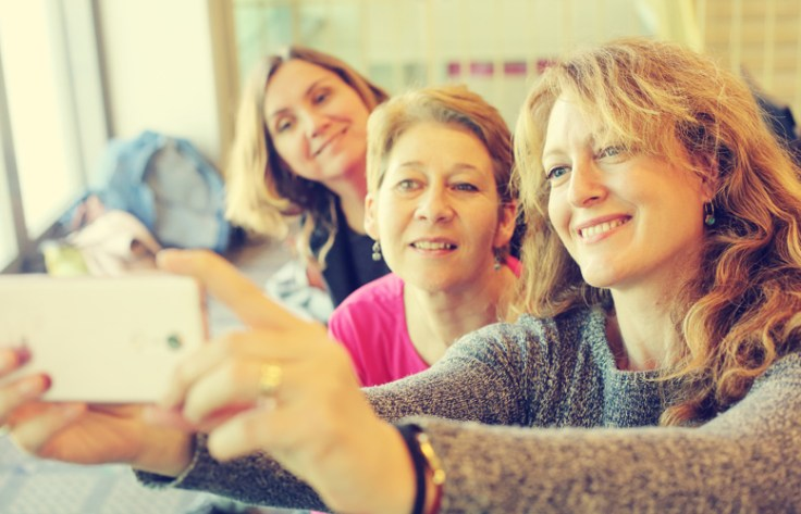 group of generation x women taking a selfie