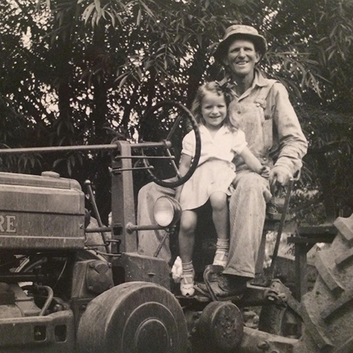 Girl and grandpa on John Deere.