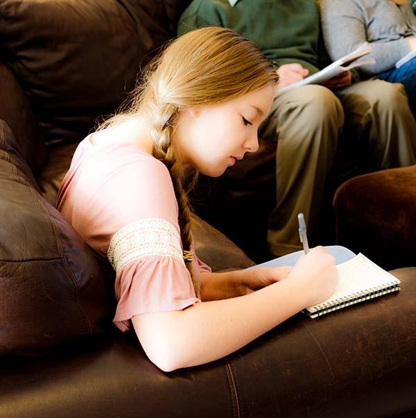 a girl teaches a boy on his ipad.