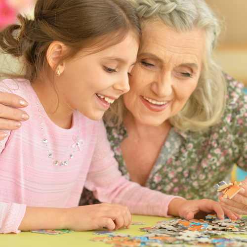 Grandmother and granddaughter put puzzle pieces together