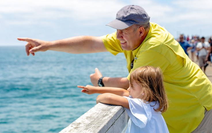 Grandfather with granddaughter by the water