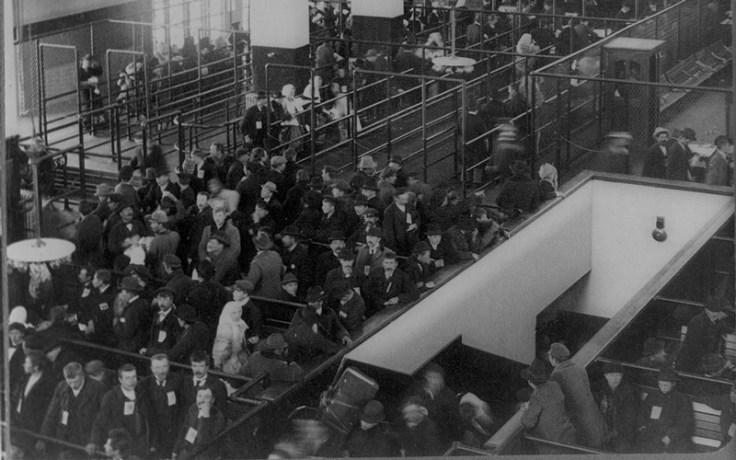 immigrants wait in line at ellis island.