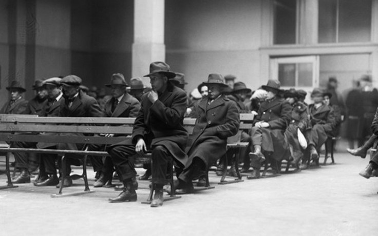 immigrants wait on benches at ellis island.