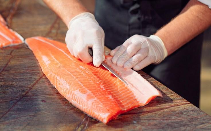 a chef prepares raw fish.