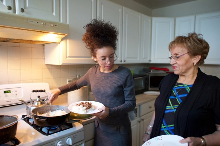 Daughter serving grandmother a home made family recipe, a fun mother's day activity.