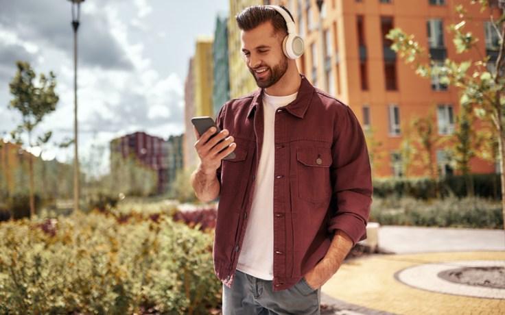 A man listens to music on his earphones, feeling nostalgic