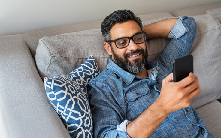 Man looks at phone on a couch