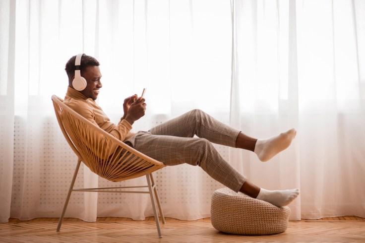 millennial man on phone wearing headphones