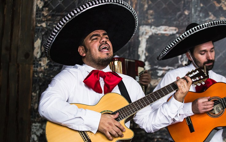Two Mexicans sing and play their guitar.