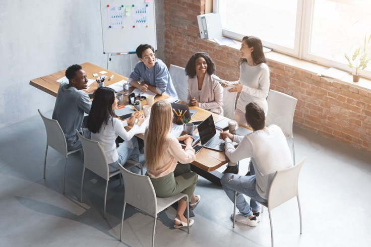 millennials working as a team at work, sitting at table together