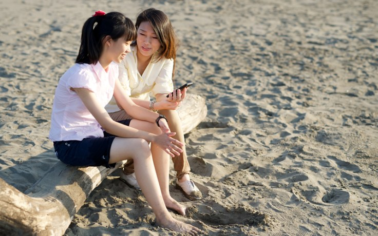Mother and daughter sitting at beach with cell phone