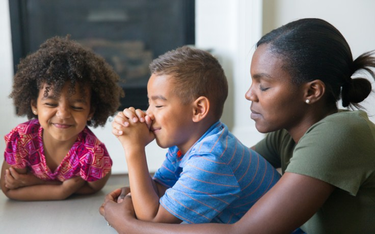 two children pray with their mother over family history