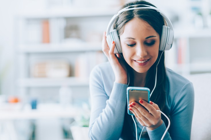 girl listening to musical time capsule, wearing headphones