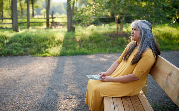 an elderly woman sits on a bench recollecting memories, a fun mother's day activity