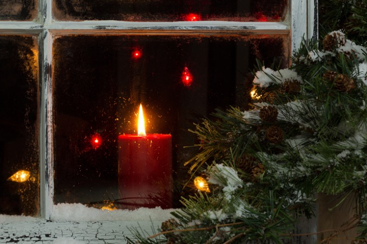 A red Christmas candle seen through a snowy window.