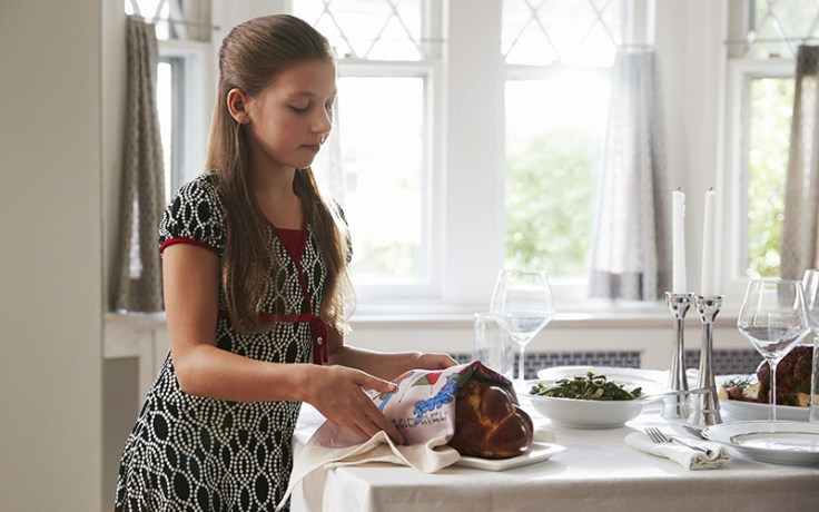 a girl sets the table for Shabbat.