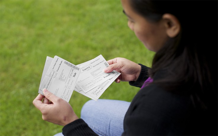 a woman holds temple ordinance cards.