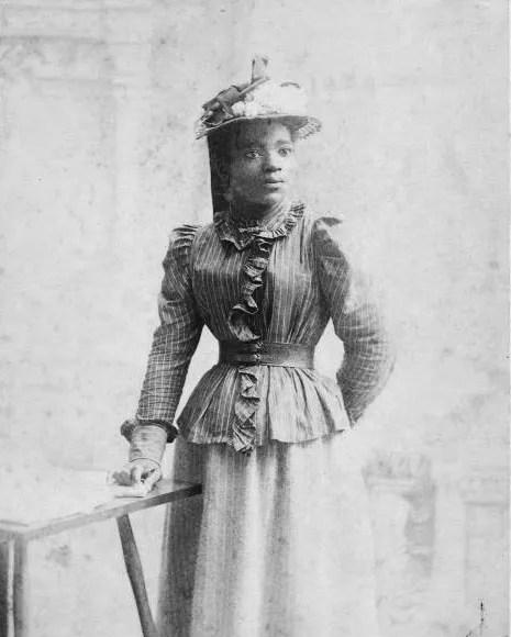 Mujer con vestido de 1900 y gran sombrero