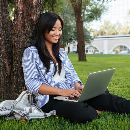 A woman sits against a tree and types on the computer