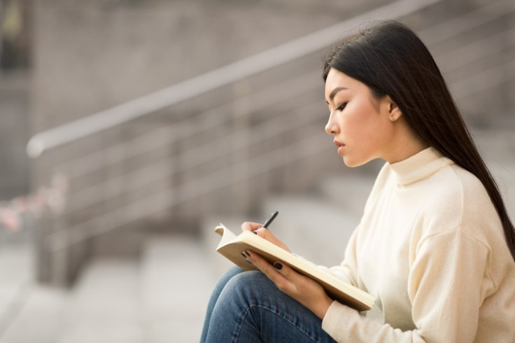 woman writing in her anxiety journal while sitting on outside steps