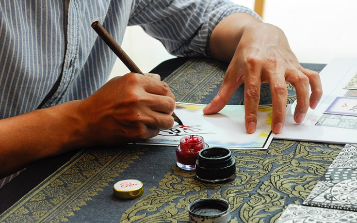 a man writes arabic calligraphy.