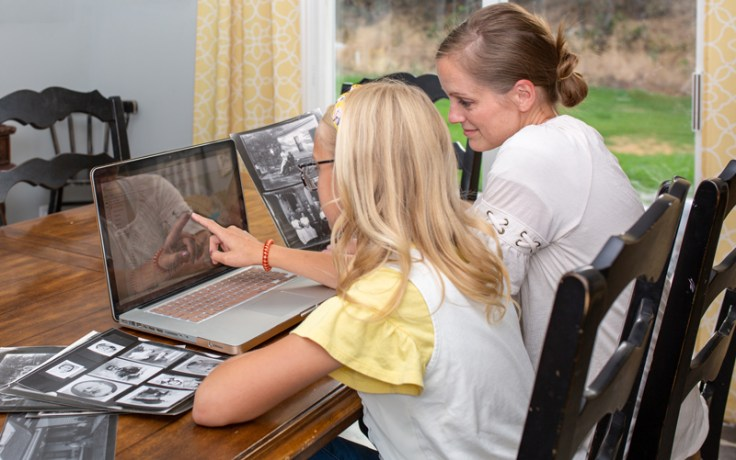A mother sits with her daughter at a computer