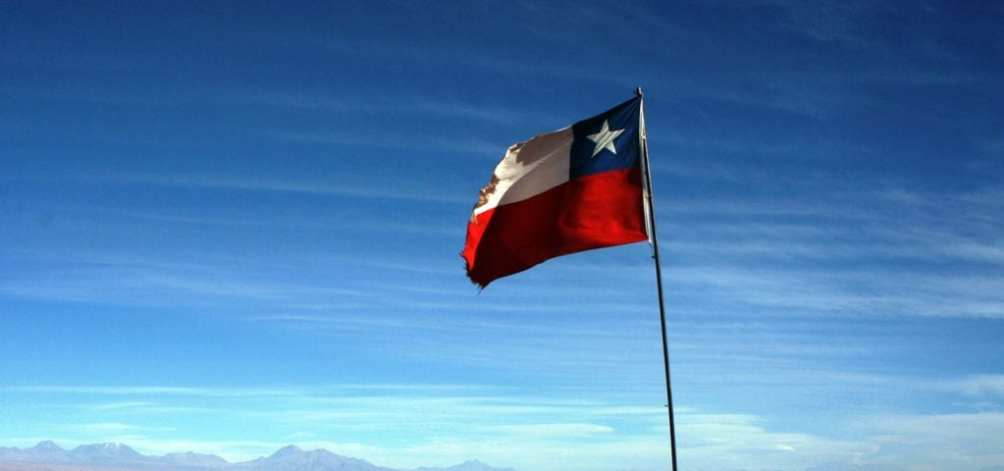 The national flag of Chile flying in the Andes Mountains.