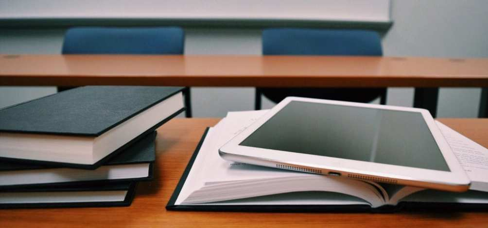 Text books and an electronic tablet sit on a desk inside of a school class room.