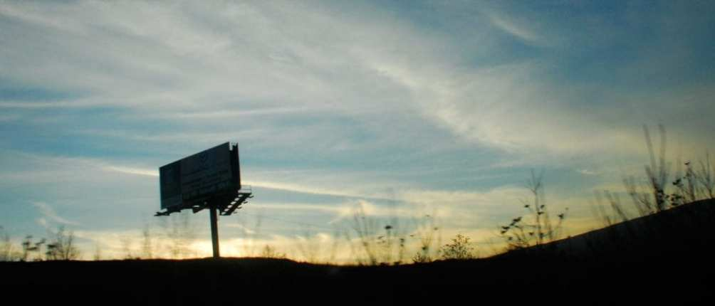A lone billboard stands silhouetted against a California horizon.