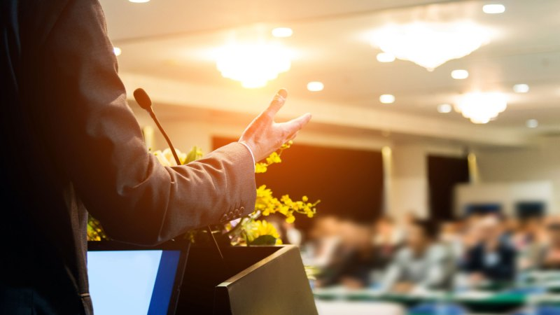 Man giving speech in front of conference of people