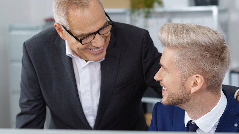Two men talking over a computer