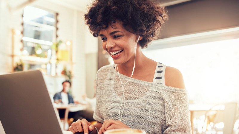 Woman with curly hair smiling and using a laptop