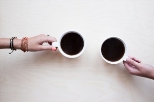 Two people's hands holding cups of coffee