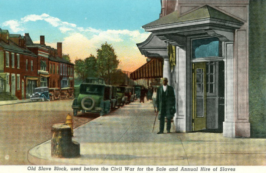 In this post card one can see a Black man who is posing next to the Fredericksburg Auction Block. This man is believed to have been sold on the block earlier in his life.