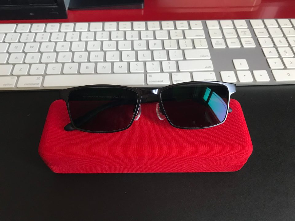 Photo of sunglasses on top of a red glasses case.