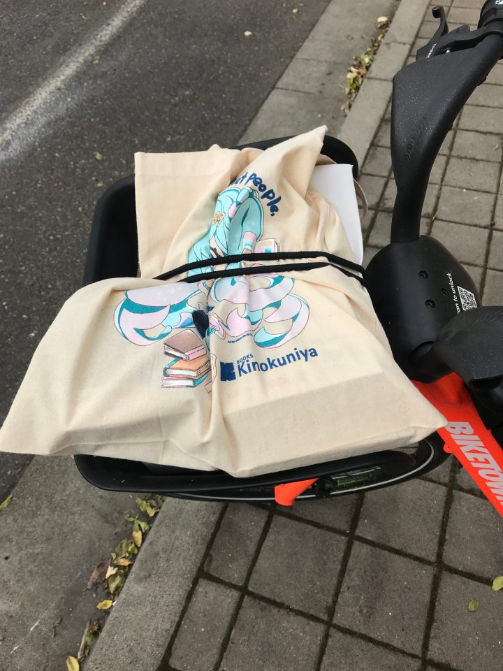 Photo of a Kinokuniya tote bag secured with bungee cord on a BIKETOWN bike.