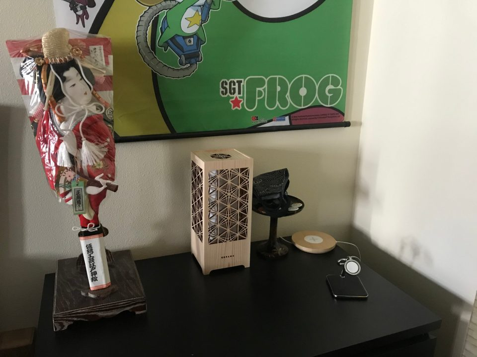 Photo of a dresser with a lamp, chargers, and decorative elements.