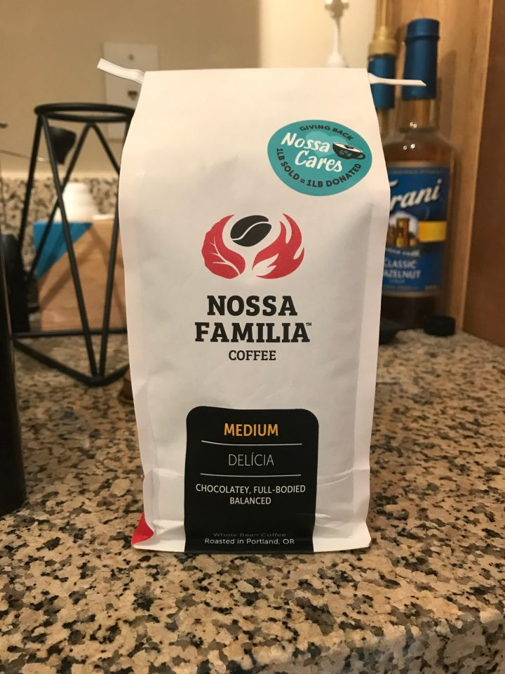 Photo of a bag of Delícia roast from Nossa Familia Coffee with a Nossa Cares sticker.